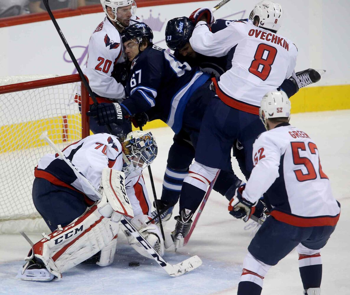 Winnipeg Jets players Michael Frolik (67) and Dustin Byfuglien are sandwiched between Washington Capitals players Troy Brouwer (20) and Alex Ovechkin in front of goaltender Braden Holtby during the first period.
