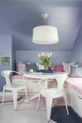 A bedroom shared by two young sisters: Designer Brian Patrick Flynn created an L-shaped window seat to keep bulky items such as tennis rackets and cheerleading gear neatly organized and easily accessible.