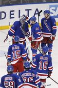 New York Rangers players line up to congratulate goalie Henrik Lundqvist, of Sweden, top left, at the end of an NHL preseason hockey game against the Philadelphia Flyers, Monday, Sept. 29, 2014, in New York. New York won 6-3. (AP Photo/Jason DeCrow)