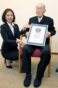 Sakari Momoi, a 111-year-old Japanese retired educator, poses for a photo after receiving a certificate from a Guinness World Records official, left, in Tokyo Wednesday, Aug. 20, 2014. Momoi was recognized as the world's oldest living man on Wednesday, succeeding Alexander Imich of New York, who died in April at the age of 111 years, 164 days. (AP Photo/Kyodo News) JAPAN OUT, CREDIT MANDATORY