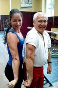 Tania Tetrault Vrga flexes with Bulgarian National Junior Weightlifting team coach Ivan Lechev. Vrga is part of a group of 12 Canadian lifters training with Bulgarian weightlifting legends.