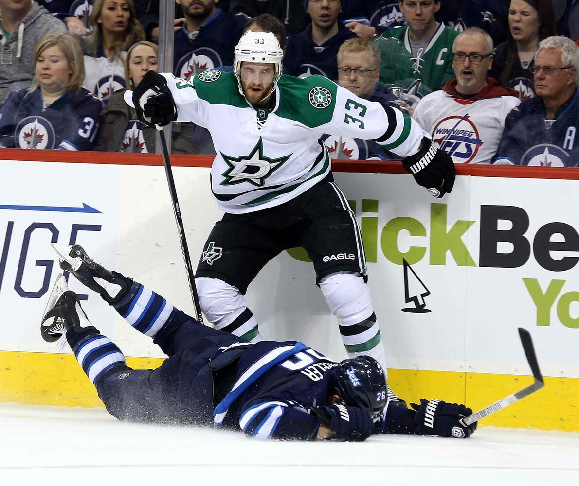 Winnipeg Jets forward Blake Wheeler hits the ice after trying to get past the Dallas Stars' Alex Goligoski during the second period. (TREVOR HAGAN / THE CANADIAN PRESS)