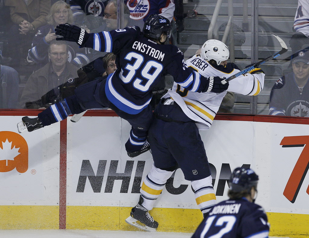 Winnipeg Jets' Tobias Enstrom (#39) and Buffalo Sabres' Mike Weber (#6) collide during the third period in Winnipeg Tuesday.  (John Woods / Winnipeg Free Press)