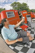 Tom McMahon and his wife, Kelly Klick, raise a toast to their ruby-red restored 1975 Boler camper-trailer, which is a hit at classic car shows.