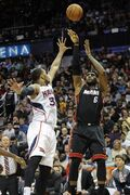 Miami Heat forward LeBron James (6) puts up a jump shot while defended by Atlanta Hawks forward Mike Scott (32) during the second half of an NBA basketball game on Saturday, April 12, 2014, in Atlanta. Atlanta won 98-85. (AP Photo/John Amis)