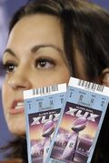 NFL Counsel Dolores F. Dibella holds up Super Bowl tickets to show the security features on them during a counterfeit ticket and merchandise news conference for NFL Super Bowl XLIX football game Thursday, Jan. 29, 2015, in Phoenix. (AP Photo/Morry Gash)