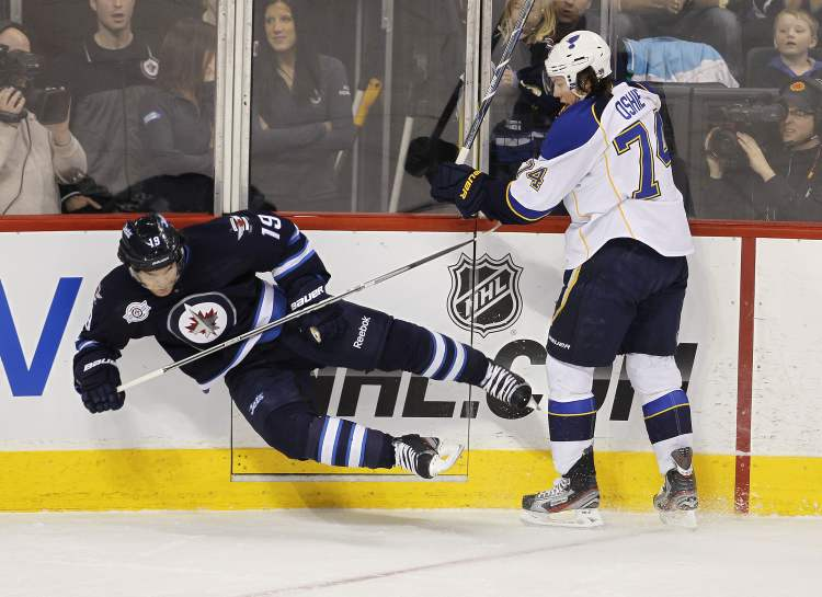The Winnipeg Jets' Jim Slater (19) is knocked over by St. Louis Blues' T.J. Oshie (74) during first period NHL action at the MTS Centre, Saturday.