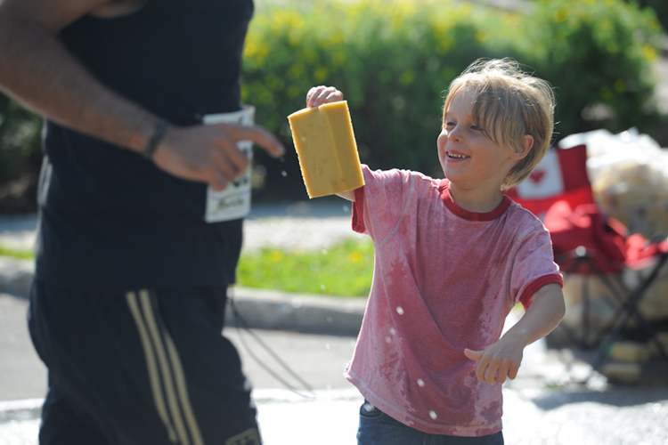 A young volunteer helps Manitoba Marathon runners keep cool.