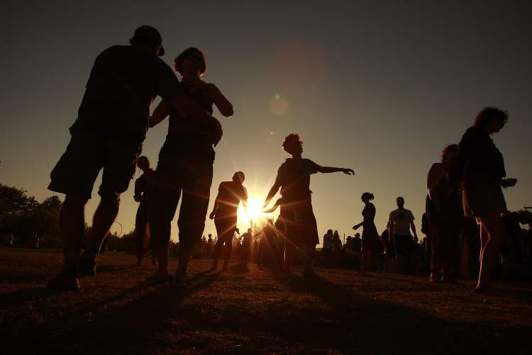 People dance as the sun sets on the last day of the Winnipeg Folk Festival.