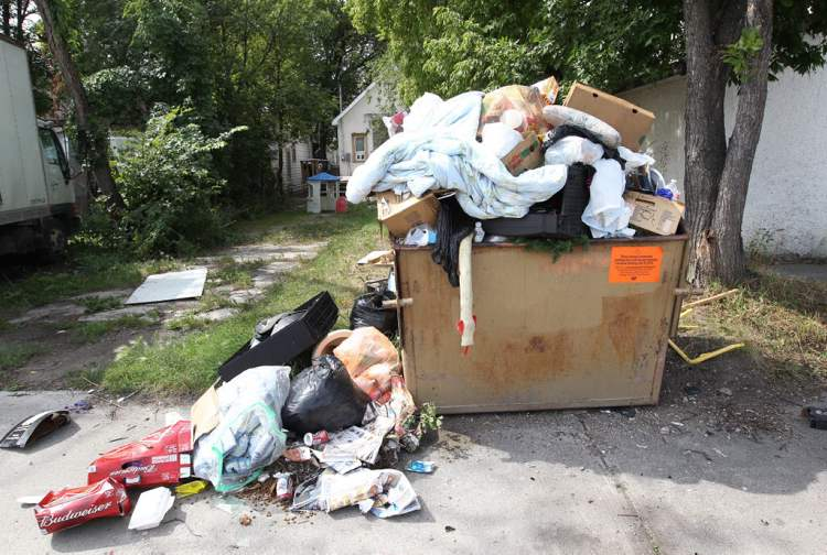 Overfilled autobins are seen in the lanes around Redwood and Aberdeen avenues. (JOE BRYKSA / WINNIPEG FREE PRESS)