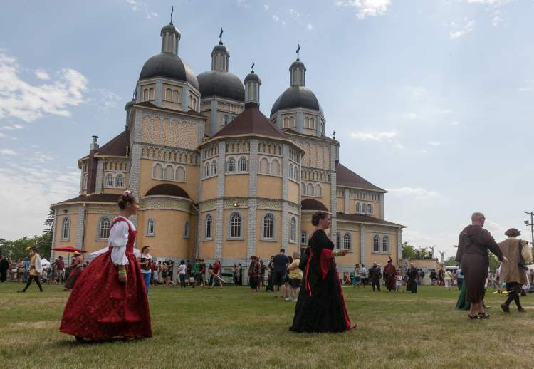 Kennedy Vincent (left) walks with her step-mother Charmagne, dressed in medieval garbs, at the 2012 Medieval Festival at the Immaculate Conception Church and Grotto on Saturday in Cooks Creek.