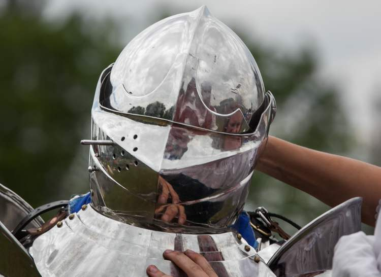 A knight's helmet is secured on his head with help during the 2012 Medieval Festival at the Immaculate Conception Church and Grotto on Saturday in Cooks Creek. Knights were on hand to demonstrate jousting for hundreds of families in attendance. (Melissa Tait / Winnipeg Free Press)