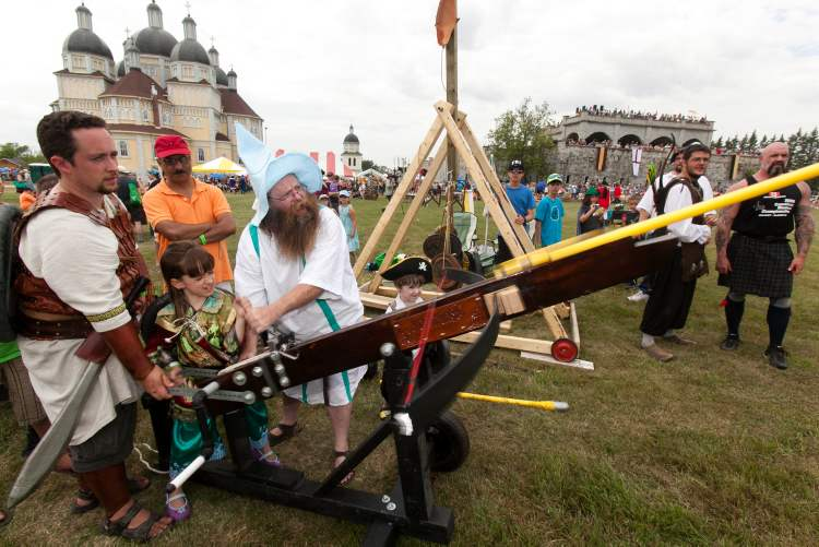 Barry James (in white) helps Eva Lauder fire an arballest with help from her dad Charles. The giant crossbow is three quarters the size of a small version used in warfare in the 15th century. The 2012 Medieval Festival held at the Immaculate Conception Church and Grotto hosted hundreds of families on Saturday in Cooks Creek.
