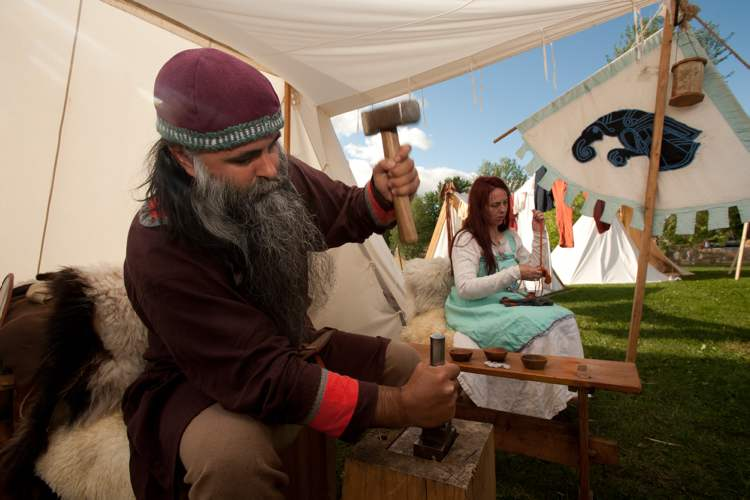 Viking reenactor Christian Arel strikes a coin while his wife, Sheena Moes, nallbinds at the Icelandic Festival in Gimli, Saturday.