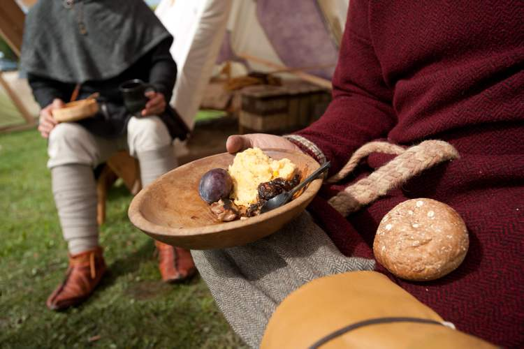 Viking reenactor Sam Shoults, who hails from Missouri, eats a meal of peas porridge, a plum, pork in a prune red wine sauce, and bread, all prepared traditionally at the Icelandic Festival in Gimli, Saturday. (COLE BREILAND / WINNIPEG FREE PRESS)