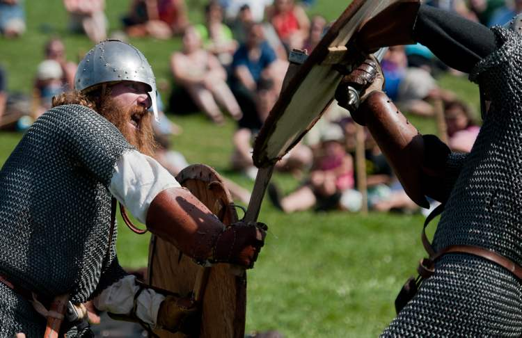 Viking reenactor James Welbourne pummels the shield of Jay Clark in a combat demonstration at the Icelandic Festival in Gimli, Monday. (COLE BREILAND / WINNIPEG FREE PRESS)