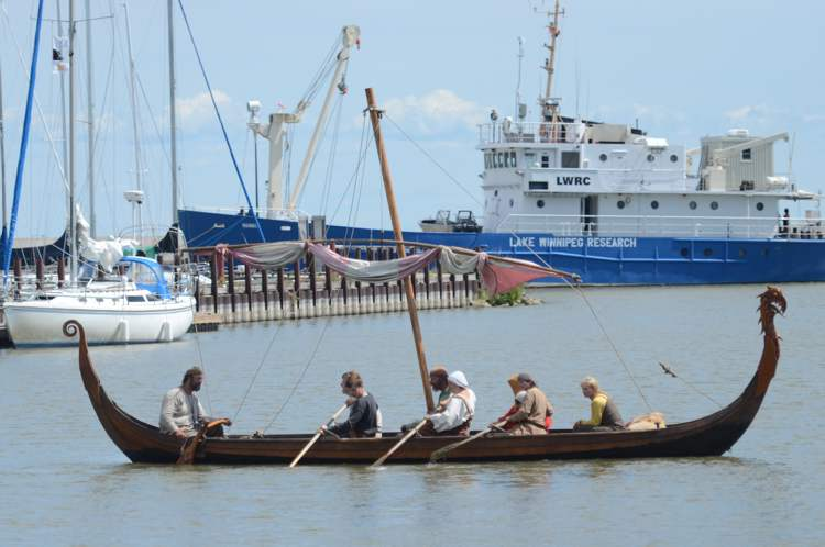 Viking reenactors take to the water in a drakkar-style war ship, named for the dragon carving at the end of the boat, at the Icelandic Festival in Gimli, Monday. (COLE BREILAND / WINNIPEG FREE PRESS)
