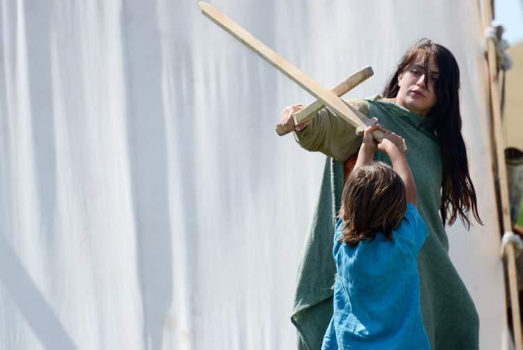Fifteen-year-old Viking reenactor Erika Jacques play sword fights with her brother among the authentic tents set up at the Icelandic Festival, Monday.