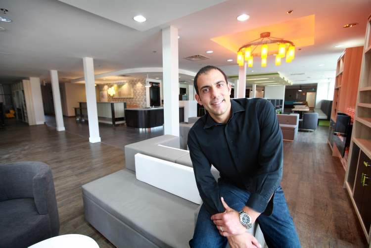 Angelo Paletta stands in the large, open-concept foyer of the new Holiday Inn Polo Park, set to open this week.