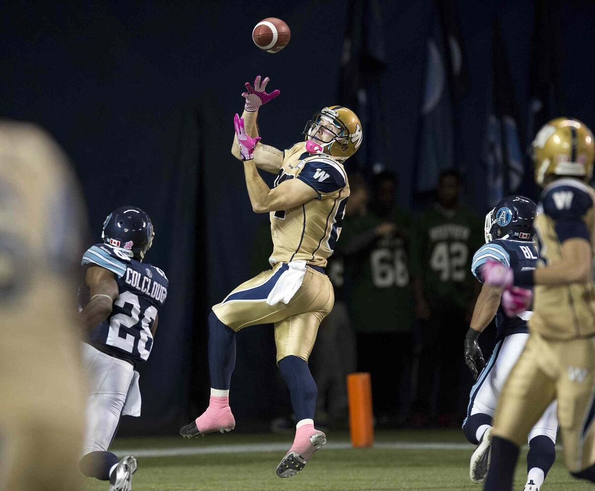 Winnipeg Blue Bombers Rory Kohlert (centre) hauls in a touchdown pass against the Toronto Argonauts during the first half. (Frank Gunn / The Canadian Press)