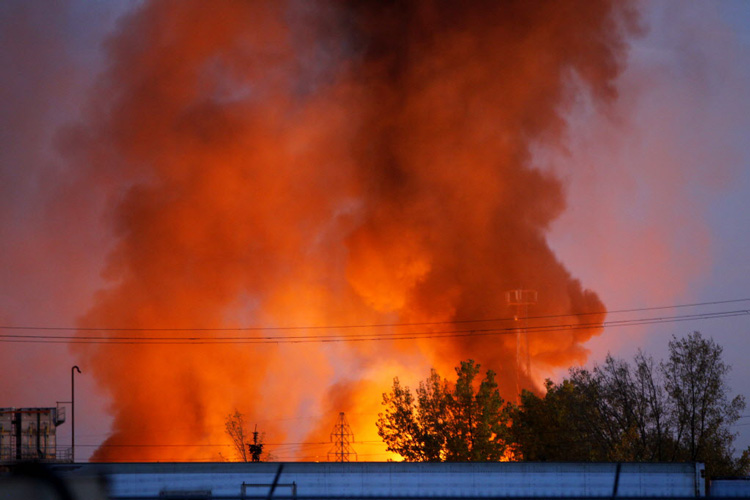 The fire in the St. Boniface-area industrial park is seen as night begins to fall. (Boris Minkevich / Winnipeg Free Press)