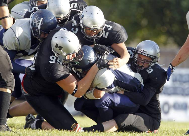 Members of the Maples Marauders defence swarm tackle West Kildonan Wolverines' Quarterback, Austin Nafostowicz, during the first half at Maples Collegiate.