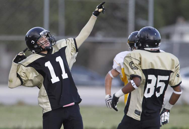 Garden City Gophers' Keenan Koswin does a Usain Bolt immitation after scoring a touchdown. Devonn Shepherd looks during their winning effort over the Dakota Lancers at Garden City Collegiate. The 2012 Winnipeg High School Football League kicked off Thursday, September 6, 2012. (TREVOR HAGAN/WINNIPEG FREE PRESS)