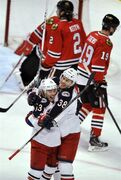 Columbus Blue Jackets' Cam Atkinson (13) celebrates with Boone Jenner (38) after Atkinson scored a goal during the first period of an NHL hockey game against the Chicago Blackhawks, Friday, March 27, 2015, in Chicago. (AP Photo/Paul Beaty)
