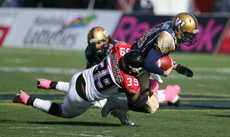 Winnipeg Blue Bombers' quarterback Joey Elliot (14) is brought down by Calgary Stampeders' Charleston Hughes (39) during the first half of CFL football action at Canad Inns Stadium, Saturday, October 13, 2012. (Trevor Hagan / Winnipeg Free Press)