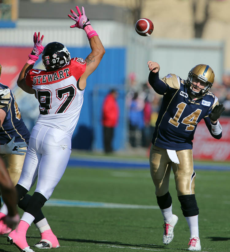 Winnipeg Blue Bombers' quarterback Joey Elliot (14) throws the ball over Calgary Stampeders' Anwar Stewart (97) during the first half of CFL football action at Canad Inns Stadium, Saturday, October 13, 2012.