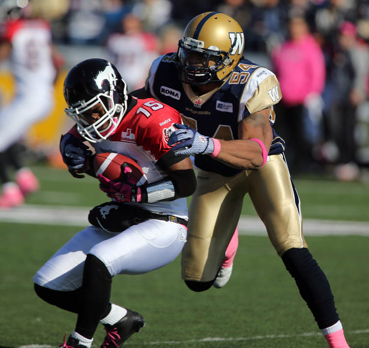 Calgary Stampeders' quarterback Kevin Glenn (15) is sacked by Winnipeg Blue Bombers' Kenny Mainor (54) during the second half of CFL football action at Canad Inns Stadium, Saturday, October 13, 2012. (Trevor Hagan / Winnipeg Free Press)