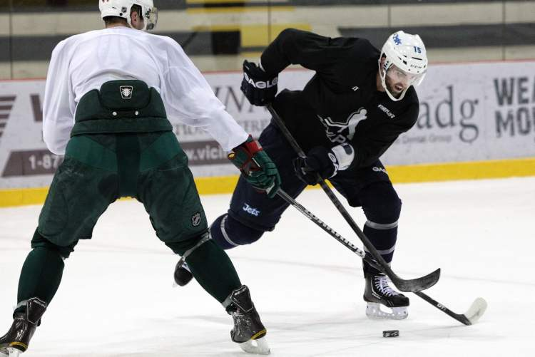 The Winnipeg Jets' Andrew Ladd (16) up against Minnesota Wild Justin Falk (44) during a training session at the MTS IcePlex Wednesday morning.