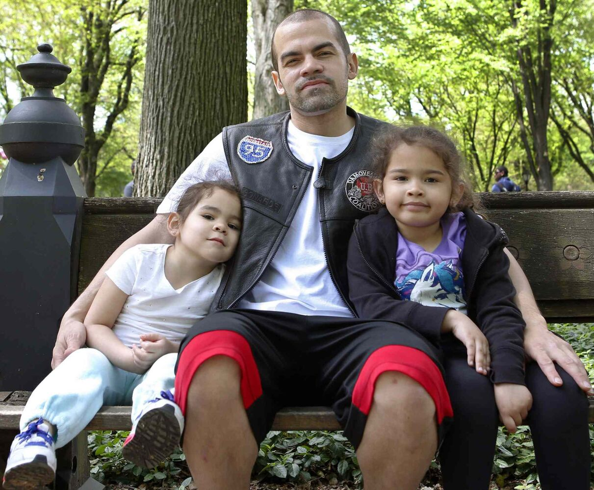 "Orlando Lopez, 34, of the Bronx borough of New York, poses for a photograph with his daughters, Sophia, 3, and Roselyann, 5, after a walkathon in New York's Central Park. When asked for his thoughts on fatherhood, Lopez, who has the girls' names tattooed on his arms, said, ""It's fun. I love it. You're with them every day. It's happiness. I've been following the same steps as my father. He was always around. I'm always around them."" (Kathy Willens / The Associated Press)"