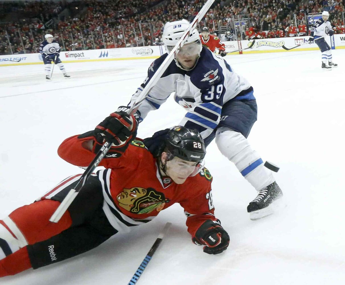 Jets defenseman Tobias Enstrom neutralizes Blackhawks right wing Ben Smith. (Charles Rex Arbogast / The Associated Press)