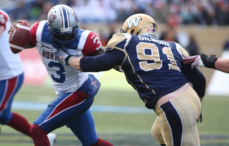 Montreal Alouettes' quarterback Adrian McPherson (3) is grabbed by Winnipeg Blue Bombers' JT Gilmore (91) during the first half of CFL action in the final game at Canad Inns Stadium, Saturday. (TREVOR HAGAN / WINNIPEG FREE PRESS)