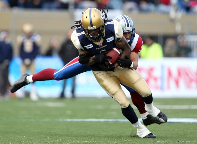 Winnipeg Blue Bombers' Kito Pohlah (1) is wrapped up by Montreal Alouettes' Chip Cox (11) during the first half of CFL action in the final game at Canad Inns Stadium, Saturday (TREVOR HAGAN/WINNIPEG FREE PRESS)