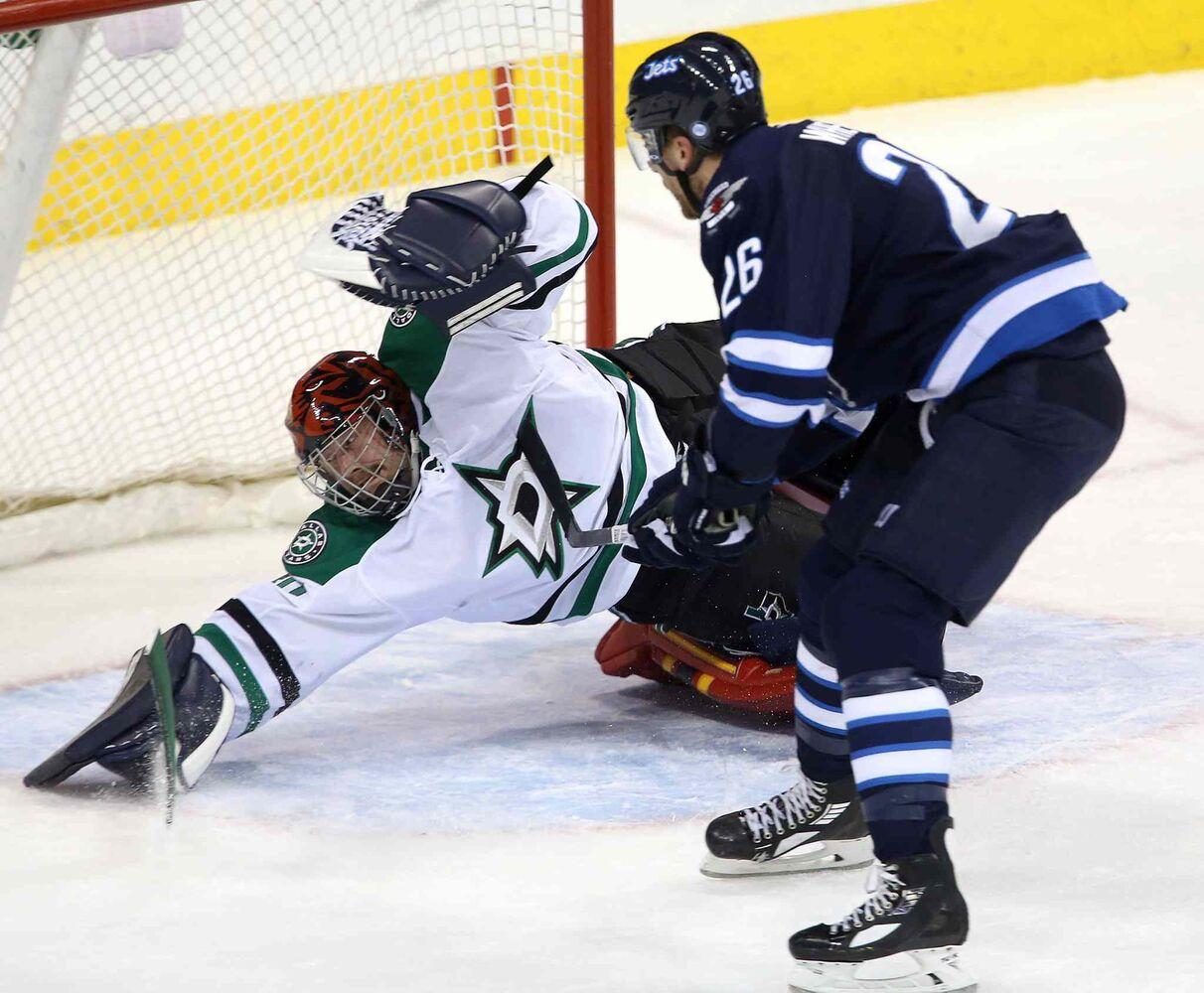 Stars goaltender Tim Thomas makes a sprawling save against Jets winger Blake Wheeler during the first period. (TREVOR HAGAN / THE CANADIAN PRESS)
