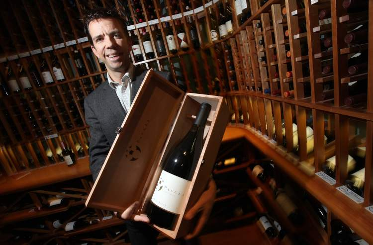 Tom Bima, general manager of the Winehouse, shows one of the more expensive bottles he expects to sell over the holidays.