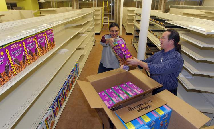 Lloyd Mason (left) and Frank Parkes stock shelves in preparation for the 'soft' opening  of Neechi Commons.
