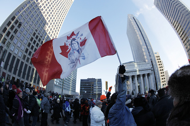 Idle No More protesters raise a flag in the air at Portage and Main. (Winnipeg Free Press)