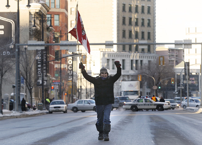 A participant approaches the crowd gathered at Portage and Main. (JOHN WOODS / WINNIPEG FREE PRESS)