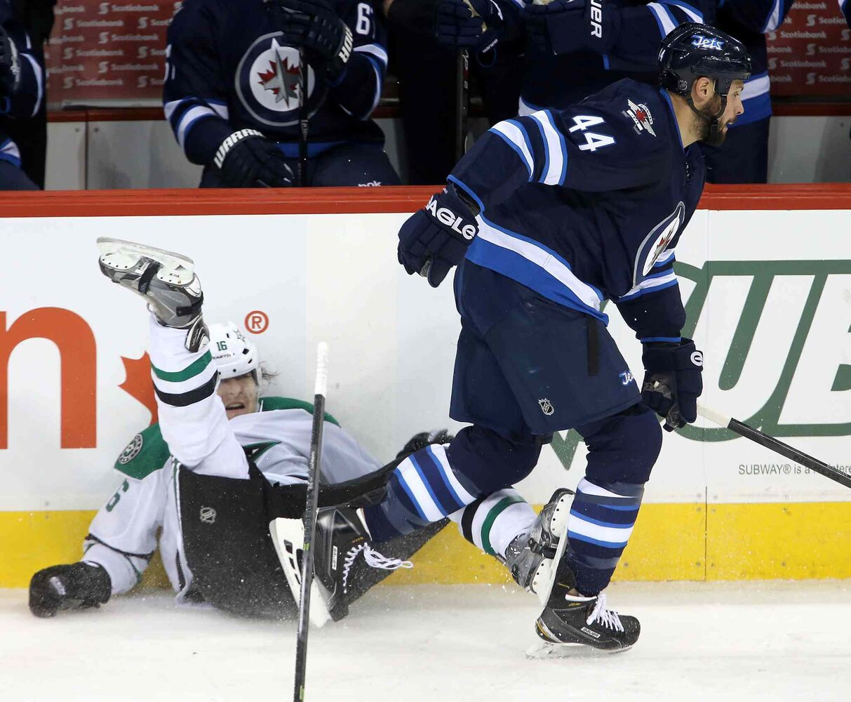 Dallas Stars forward Ryan Garbutt is pasted into the boards by Winnipeg Jets defenceman Zach Bogosian in the first period. (TREVOR HAGAN / THE CANADIAN PRESS)