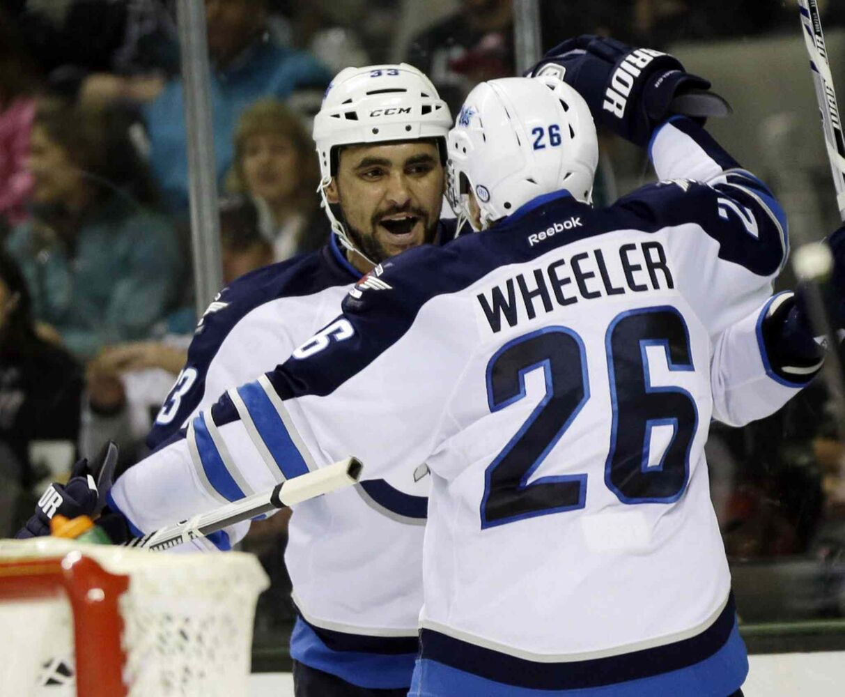 Winnipeg Jets' Dustin Byfuglien, left, celebrates his goal with teammate Blake Wheeler (26) during the second period.  (Marcio Jose Sanchez / The Associated Press)