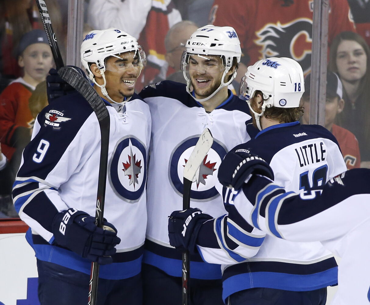 Winnipeg Jets' Michael Frolik, centre, celebrates his first-period goal against the Calgary Flames with Evander Kane, left, and Bryan Little during Friday's game.