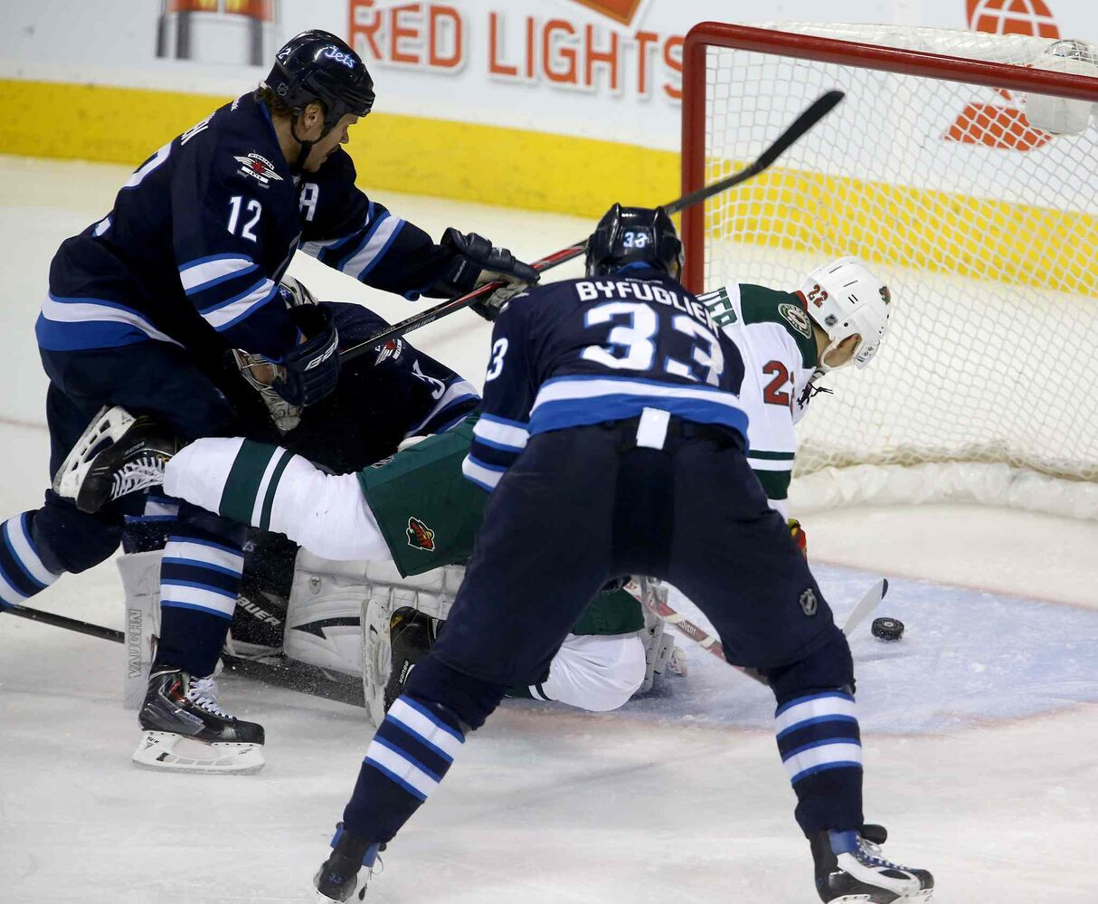 Minnesota Wild's Nino Niederreiter (right) gets through Winnipeg Jets skaters Olli Jokinen (left) and Dustin Byfuglien (centre) to beat goaltender Ondrej Pavelec during the third period. (TREVOR HAGAN / WINNIPEG FREE PRESS)