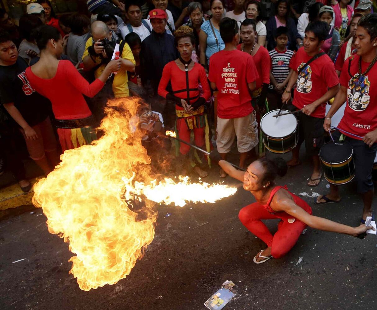 A fire-eater performs in front of a business establishment in celebration of Chinese New Year at Manila's Chinatown district of Binondo, Philippines on Friday, Jan. 31, 2014.