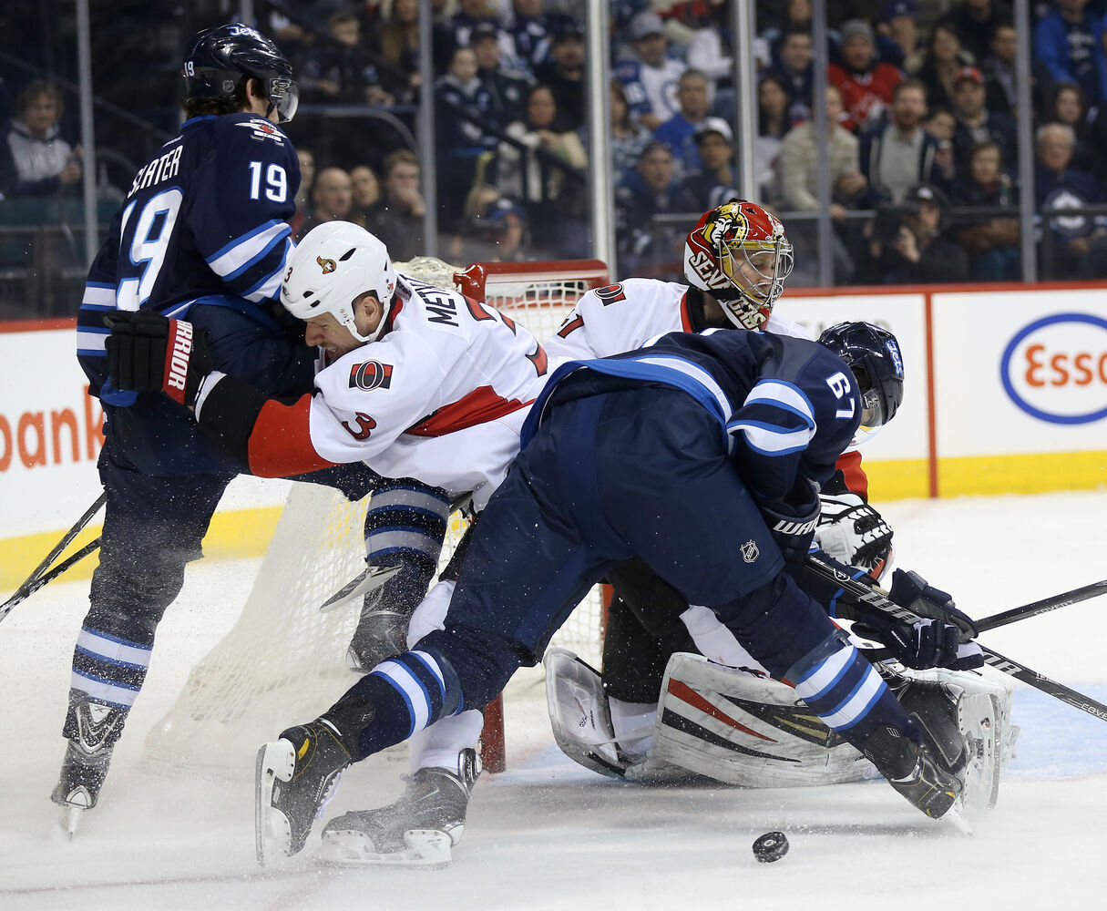 Winnipeg Jets' Jim Slater (19) and Michael Frolik (67) battle with Ottawa Senators' Marc Methot (3) in front of goaltender Craig Anderson (41) during second period NHL action.  (TREVOR HAGAN / WINNIPEG FREE PRESS)