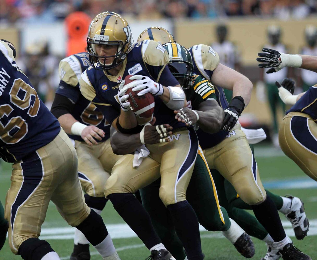 Winnipeg Blue Bombers' quarterback Drew Willy gets wrapped up in the arms of Edmonton Eskimos' #90 Almondo Sewell in the second quarter of Thursday's game. (Phil Hossack / Winnipeg Free Press)