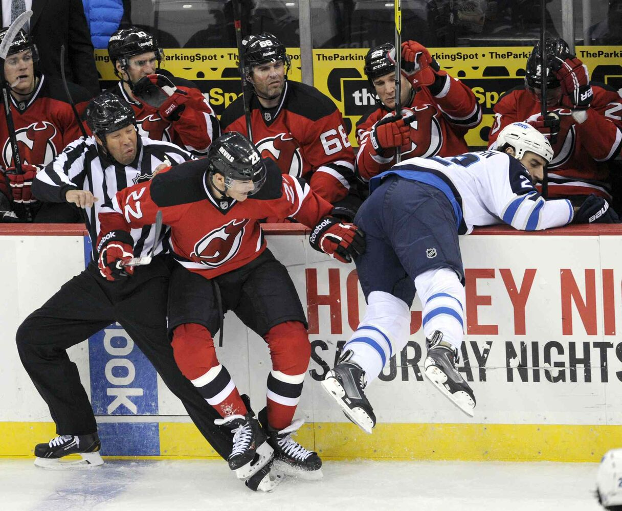 New Jersey Devils' Eric Gelinas (22) collides with linesman Jay Sharrers after checking Winnipeg Jets forward Chris Thorburn into the boards during the third period. (BILL KOSTROUN / THE ASSOCIATED PRESS)