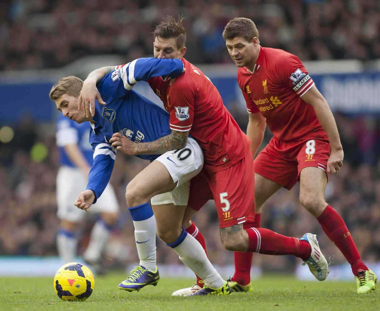 Everton's Gerard Deulofeu (left) battles for the ball against Liverpool's Daniel Agger (centre) as Steven Gerrard looks on during their English Premier League soccer match at Goodison Park Stadium, Liverpool, England on Saturday. (Jon Super / The Associated Press)